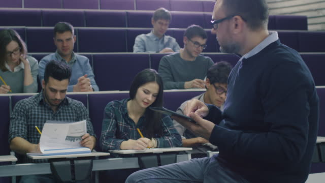 College professor is teaching a class of multi-ethnic students and checking a tablet computer. video