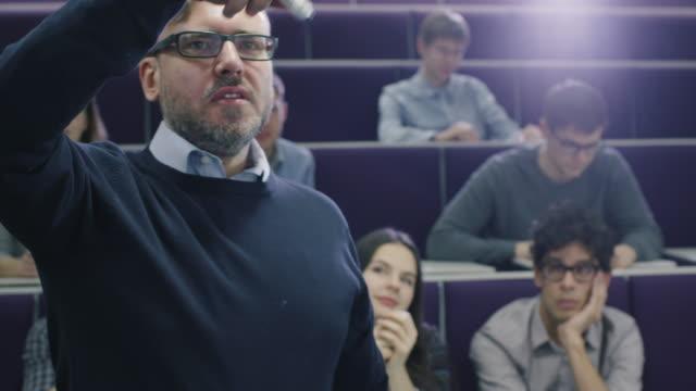 大学教授はマーカーで机を指差しながら多民族の学生のクラスを教えます。 ビデオ
