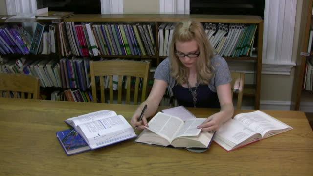 college student doing research - endast en tonårsflicka bildbanksvideor och videomaterial från bakom kulisserna