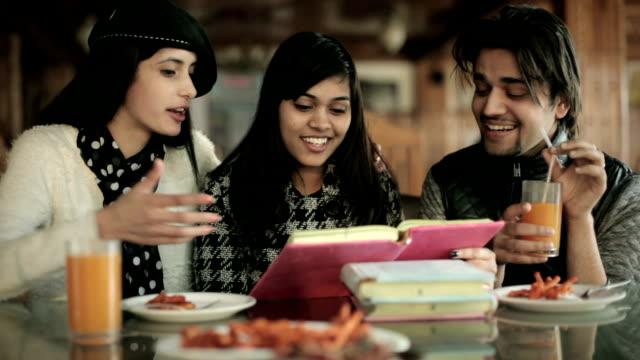 Amigos de estudiante de Colegio aprender y enseñar juntos en un restaurante. - vídeo