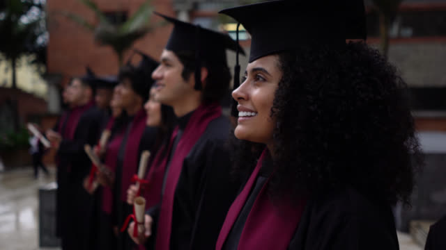 大學生在畢業典禮上拿著畢業證書,驕傲地和快樂 - 文憑 個影片檔及 b 捲影像