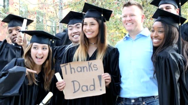 """vídeos de stock, filmes e b-roll de estudantes universitários segura sinal """"obrigado papai"""" após a cerimônia de formatura. - agradecimento"""