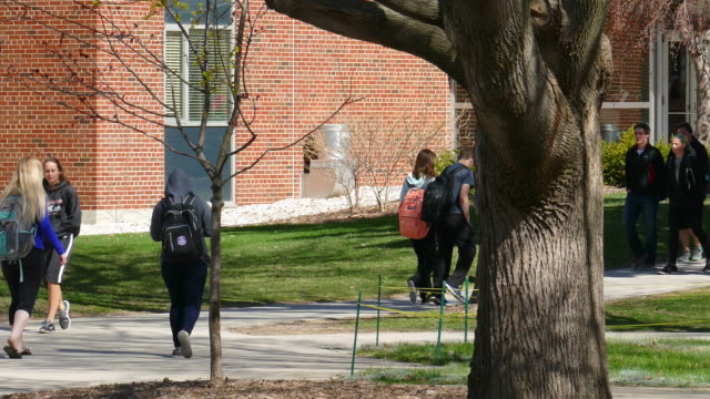 College Students Walking Around Busy Campus on Cool Spring Day Crowd of college students walking around bustling campus on cool, sunny spring day. campus stock videos & royalty-free footage