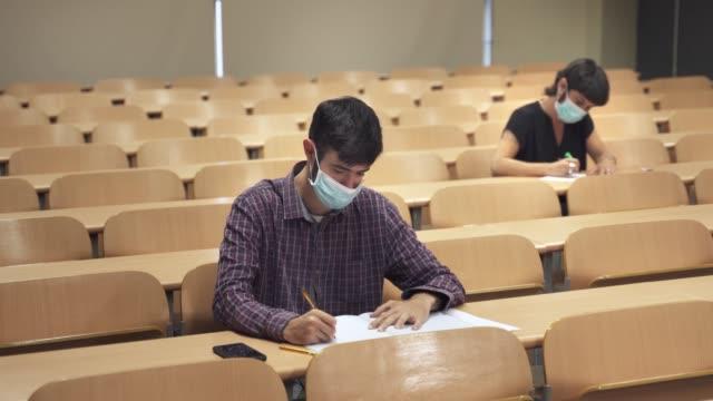 vídeos y material grabado en eventos de stock de los estudiantes universitarios que llevan máscaras faciales asisten a la conferencia en la universidad. medidas de distanciamiento social y aula vacía debido a la pandemia de coronavirus - universidad