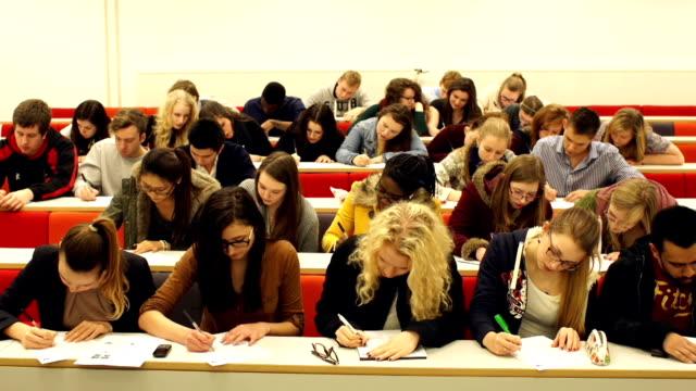 studenti universitari scrivere in university aula universitaria - esame università video stock e b–roll