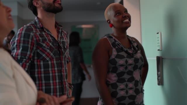 vídeos de stock e filmes b-roll de collegues walking and waiting for elevator in building hall - envolvimento dos funcionários
