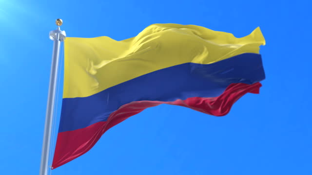 vídeos de stock e filmes b-roll de colombia flag waving at wind in slow with blue sky, loop - colômbia