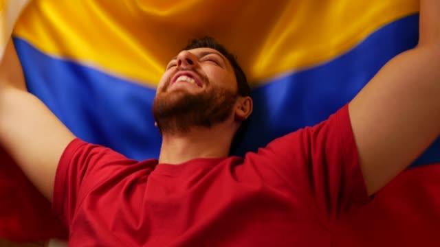 vídeos y material grabado en eventos de stock de fan colombiano celebra con la bandera de colombia - colombia