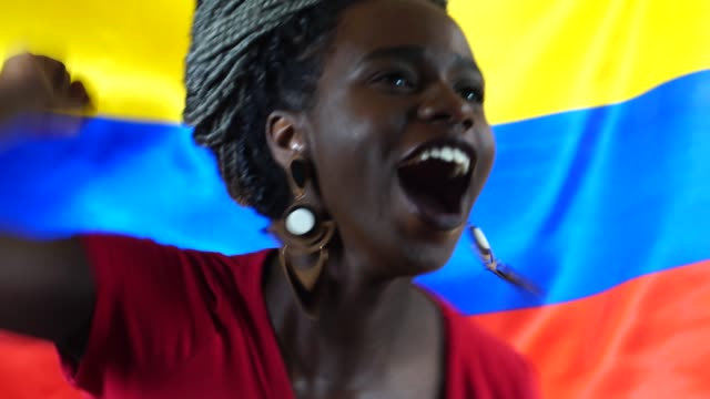vídeos de stock e filmes b-roll de colombian young black woman celebrating with colombia flag - soccer supporter portrait