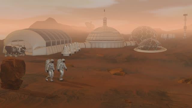 koloni på mars. två astronauter gå på ytan av mars. utforska mission till mars. futuristisk kolonisering och rymdutforskning koncept. - mars bildbanksvideor och videomaterial från bakom kulisserna
