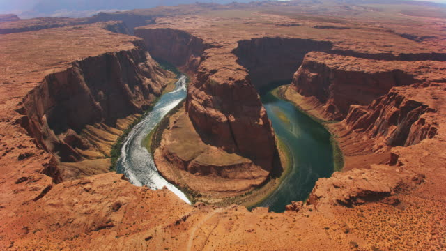 aerial colorado river shining in the sun, running around the horseshoe bend in arizona, usa - parco nazionale video stock e b–roll
