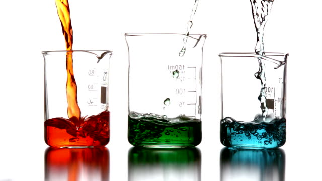 Colored chemicals pouring into beakers Colored chemicals pouring into beakers in slow motion beaker stock videos & royalty-free footage
