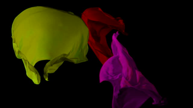 Colored fabrics flowing in the air on black background. Slow motion video