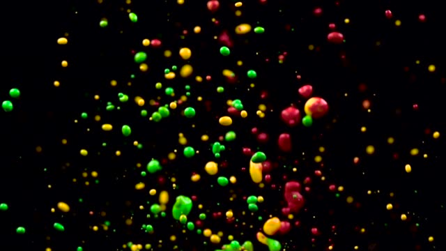 Colored fountain of multicolored water jets. Black background. Slow motion