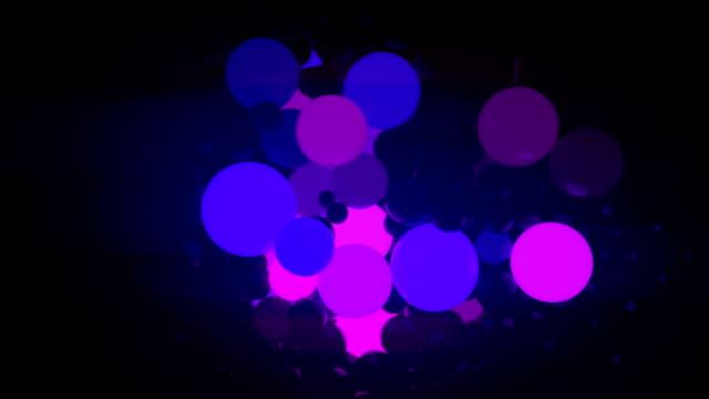 vídeos de stock, filmes e b-roll de bolas coloridas brilhantes sobre fundo preto. renderização 3d de animação digital. 4k, resolução hd ultra - contrastes