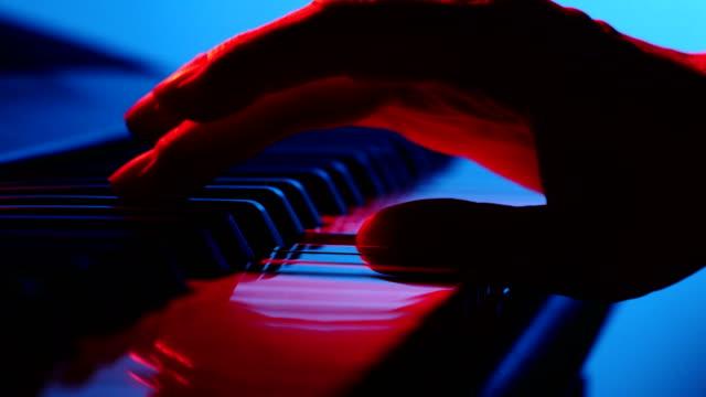 vidéos et rushes de main colorée jouant sur le synthétiseur de piano close up - synthétiseur