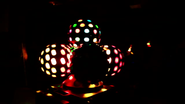 Colored light show in the dark at party. Close-up view of colored light balls twisting, shyning at disco club video