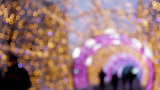 stockvideo's en b-roll-footage met gekleurde lampen boog wazig licht flikkeren in heldere kleuren. kerstmis en nieuwjaar vakantie achtergrond - boog architectonisch element