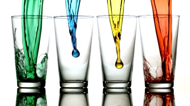Colored liquids pouring into glasses, slow motion video