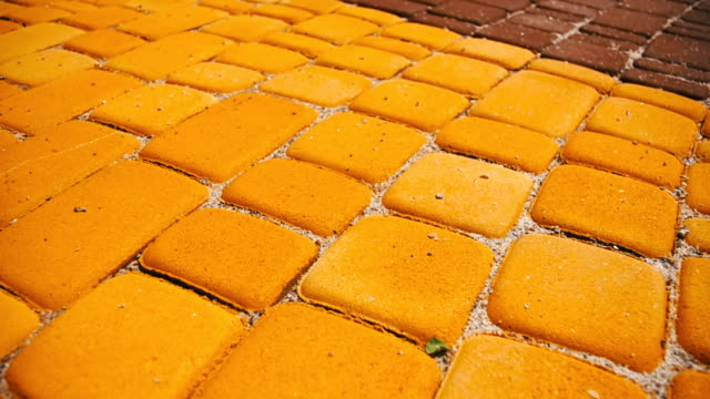 Colored Paving Stones in a Park in Motion Colored paving stones in a park in motion. Background of colored stone tiles on the sidewalk. Yellow and red stone blocks on a summer day. brick stock videos & royalty-free footage
