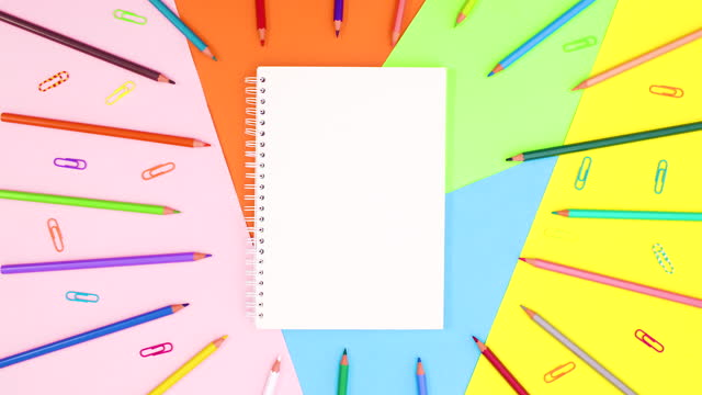 Colored pencils and paper clips move around notebook. Stop motion