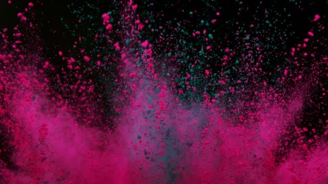 vídeos y material grabado en eventos de stock de explosión de polvo coloreado sobre fondo negro. - rosa color