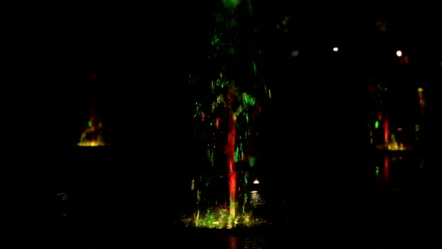 Colored water night fountain dancing with lights multicolored blur footage background, close up, shallow depth of the field, 59,94 fps video