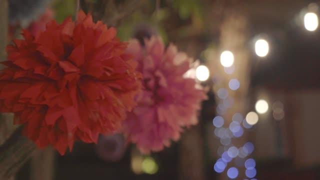 Colorful adorn flower swing on tree in garden. video