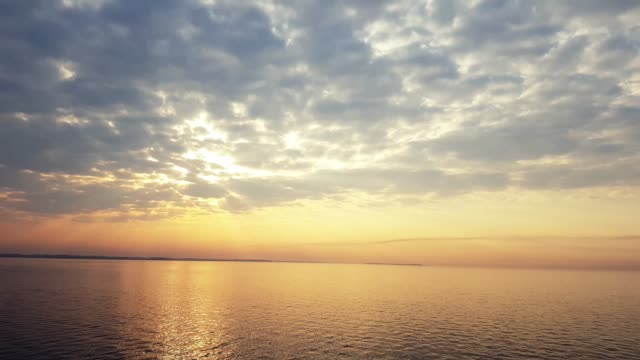 Colorful amazing dramatic sky with clouds at sunrise over river surface video