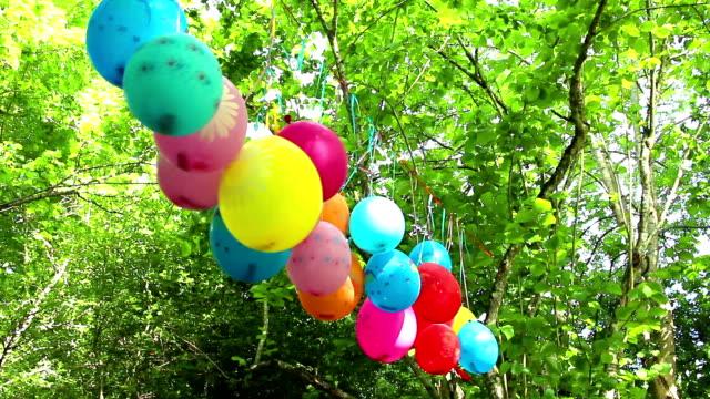 vidéos et rushes de ballons colorés garland sur le feuillage vert en arrière-plan - art et artisanat