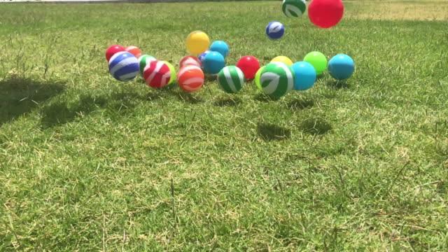 Esferas coloridas que saltam no jardim - vídeo