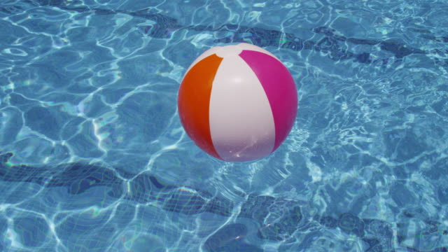 Colorful beach ball floating in pool.