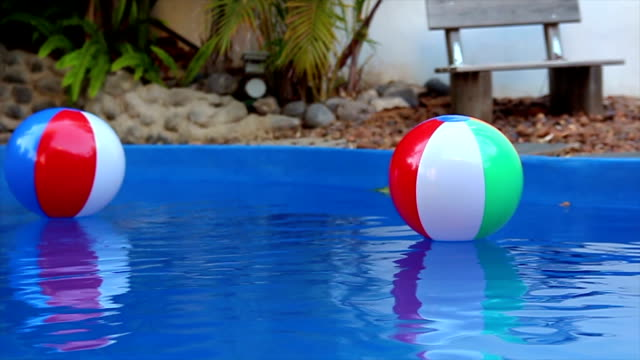 Colorful beach balls floating in pool in slow motion video