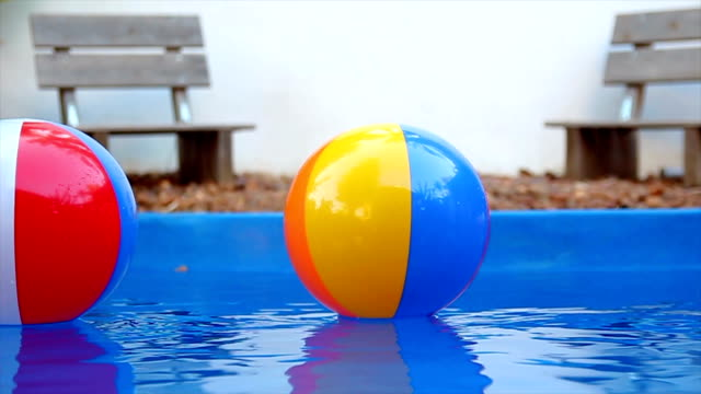 colorful beach balls floating in pool in slow motion - inflatable ring bildbanksvideor och videomaterial från bakom kulisserna