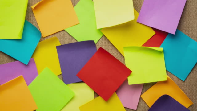 vídeos de stock e filmes b-roll de colorful blank sticky notes being dropped onto canvas board - stop motion - papel adesivo