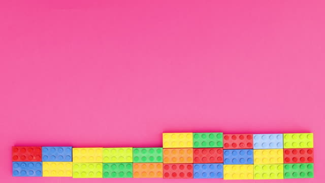 Colorful bricks making wall on pink background - Stop motion