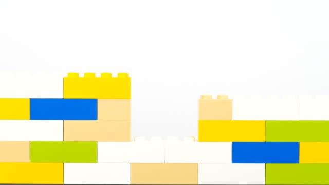 colorful bricks making wall on white background - klocek filmów i materiałów b-roll