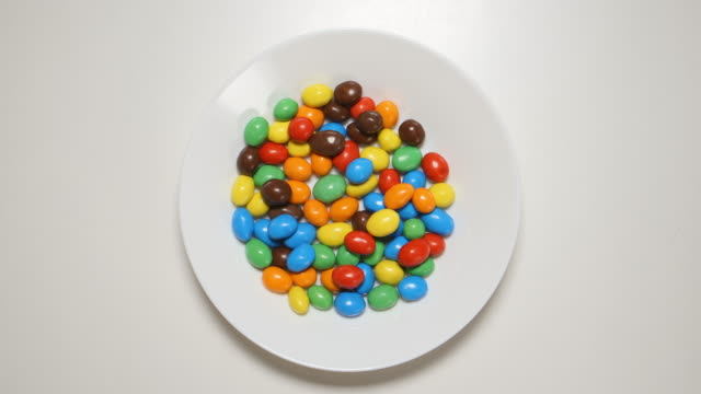 TOP VIEW: Colorful candies appear on a white dish on a white table (stop motion) video