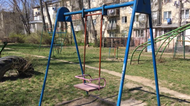 Colorful children's swing swinging without a child Colorful children's swing swinging without a child outdoor play equipment stock videos & royalty-free footage
