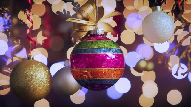 Colorful Christmas adorns and baubles on defocused Christmas lighting background Colorful Christmas adorns and baubles on defocused Christmas lighting background. Christmas is a time for family and friends to get together and exchange gifts.  A Christian holiday honoring the birth of Jesus Christ, Christmas evolved over two millennia into a worldwide religious and secular celebration. Christmas Day is a holiday in many, but not all, countries. Many homes have Christmas trees and other decorations in the weeks leading to Christmas Day. Some workplaces hold Christmas parties prior to December 25. navidad stock videos & royalty-free footage