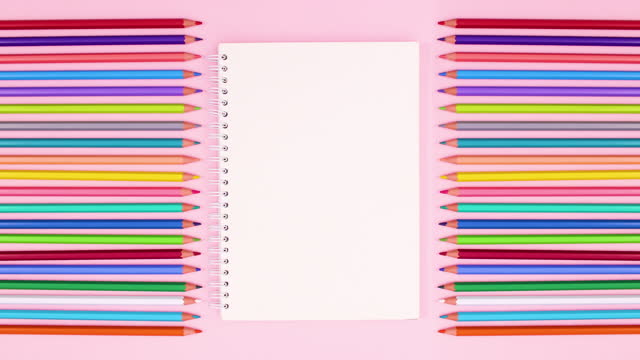 Colorful colored wooden pencils on pink theme. Drawing stationery stop motion