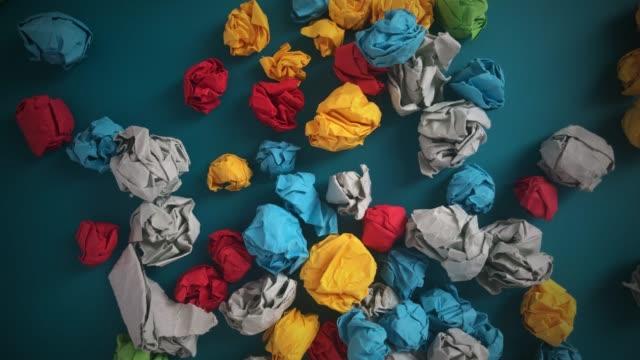 Colorful crumpled paper balls falling