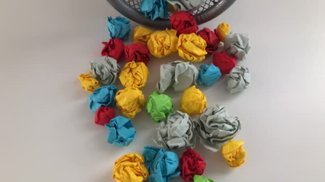 Colorful crumpled paper balls in a trash can