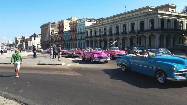 bunte kubanische autos unterwegs im zentrum von havanna - havanna stock-videos und b-roll-filmmaterial