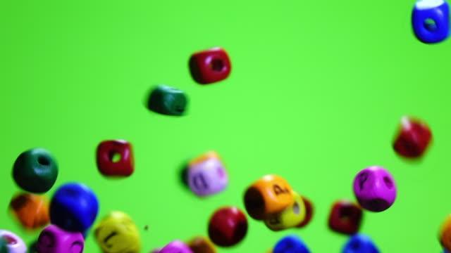 Colorful dice exploding on chroma key slow motion