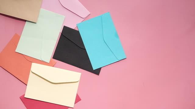 färgglatt kuvert på rosa bakgrund uppifrån och ned - kuvert bildbanksvideor och videomaterial från bakom kulisserna