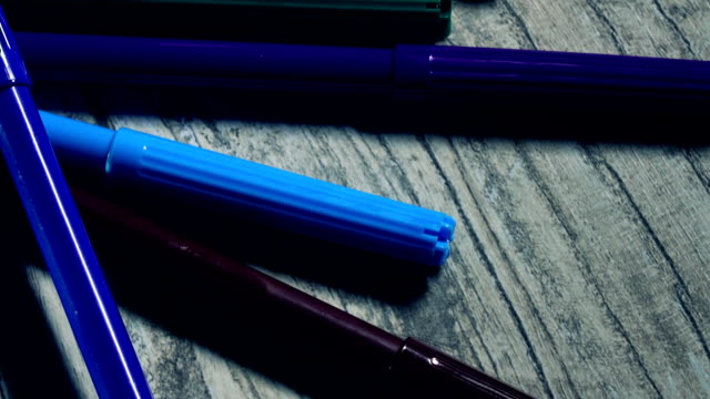 Colorful felt pens on wooden table. Cold colors. FullHD closeup pan shot video