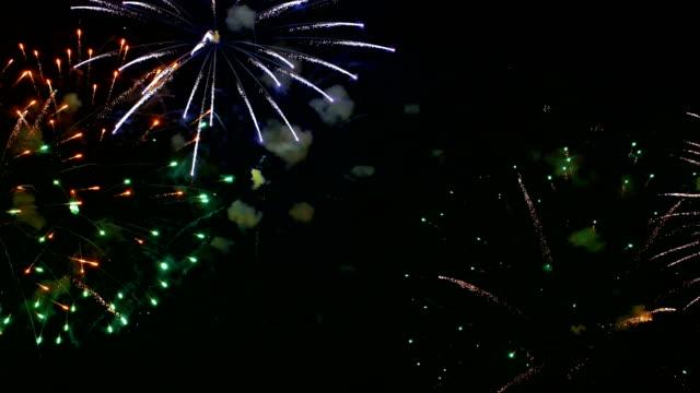 buntes feuerwerk explodiert in den nachthimmel. feiern und veranstaltungen in leuchtenden farben. - weltraum und astronomie stock-videos und b-roll-filmmaterial