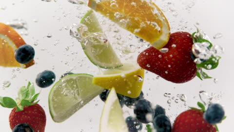 Colorful Fruit Salad Splashing Mixed Fruit: Strawberries, Blueberries, Lemon, Lime, and Orange Slices dropped into a fish tank, 1080p 120fps. fruit stock videos & royalty-free footage