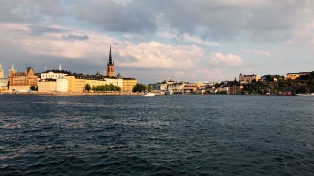 färgglada gamla stan utsikt från stockholms stadshus-djurgården färja passerar i viken och riddarholmskyrkan i bakgrunden - ferry lake sweden bildbanksvideor och videomaterial från bakom kulisserna